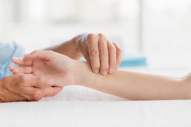 Masajista recortada dando masaje de manos a mujer