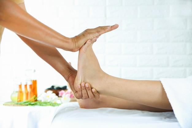 Masajista utiliza dos manos para masaje de pies con mujer joven