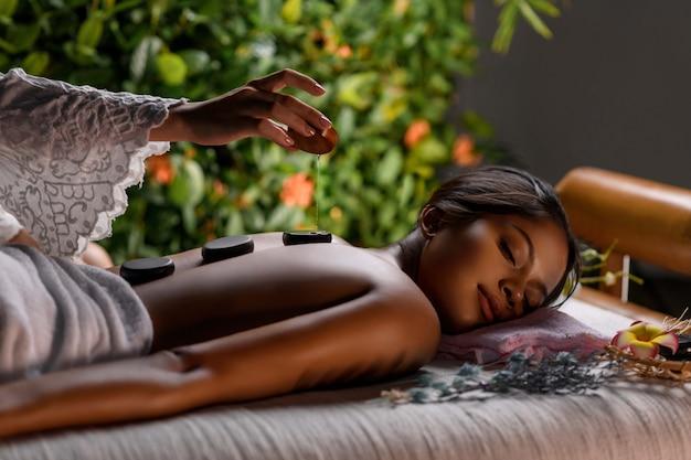 Masajista vierte aceite aromático sobre piedras para terapia de piedras acostado en la espalda de una linda chica interracial