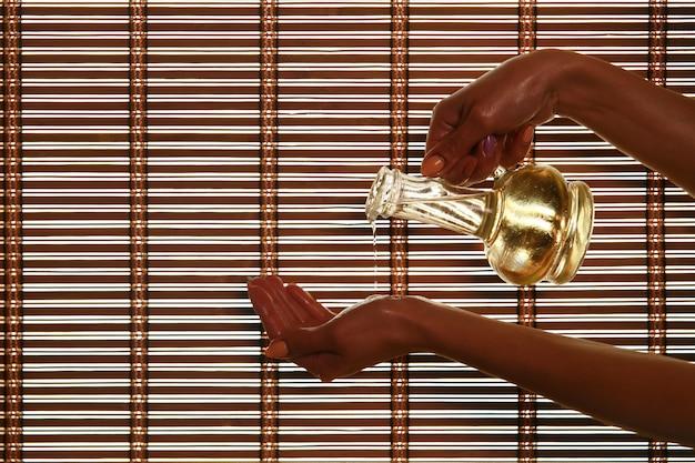 Masajista vierte aceite de fragancia en la palma