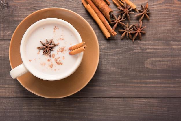 Masala chai con especias canela, cardamomo, jengibre, clavo y anís estrellado en mesa de madera