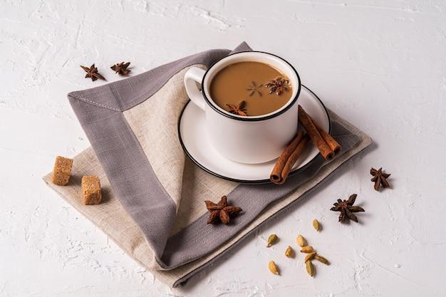 Masala chai té en una taza, especias de anís, azúcar en la mesa de hormigón blanco.