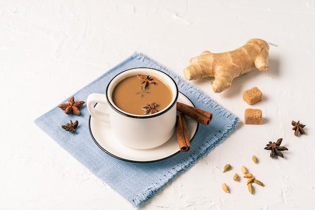 Masala chai té en una taza, especias de anís, azúcar sobre fondo blanco de mesa.