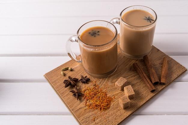 Masala chai té en tazas, azúcar moreno, canela, anís y badian sobre fondo blanco de mesa.