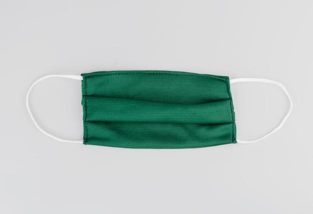 Máscara de algodón verde o máscara de tela sobre fondo gris. polvo protector y virus. máscara preventiva de coronavirus de algodón. objeto en el fondo. concepto de salud.