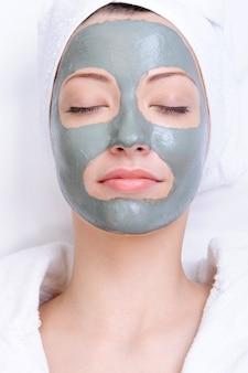Máscara de arcilla en el primer plano del rostro femenino hermoso joven