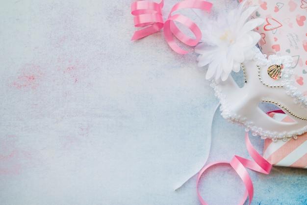 Máscara blanca compuesta con cintas de color rosa.
