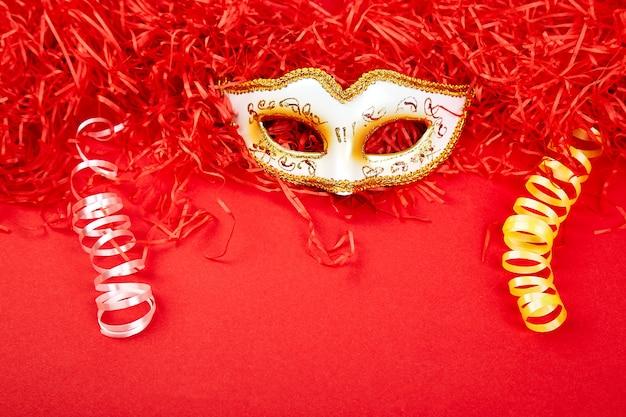 Máscara de carnaval amarillo y blanco sobre fondo rojo.