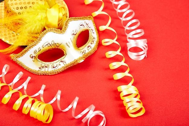 Máscara de carnaval amarillo y blanco sobre rojo.