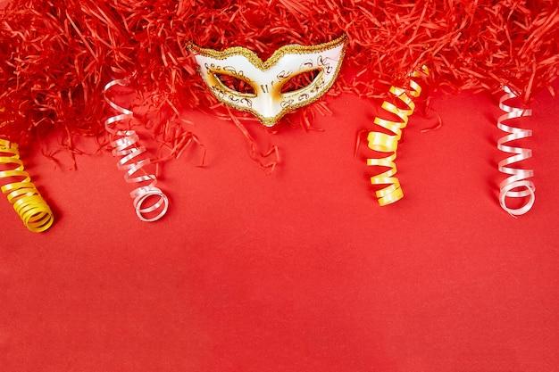Máscara de carnaval amarillo y blanco sobre rojo