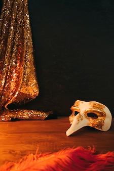 Máscara de carnaval blanca y dorada con plumas y textiles de lentejuelas sobre fondo negro