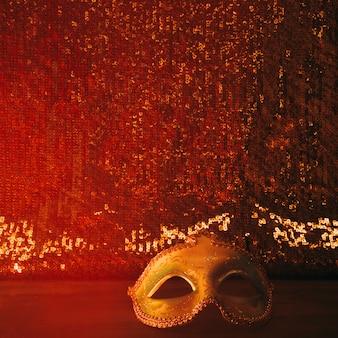 Máscara de carnaval brillante contra tejido textil rojo brillante.