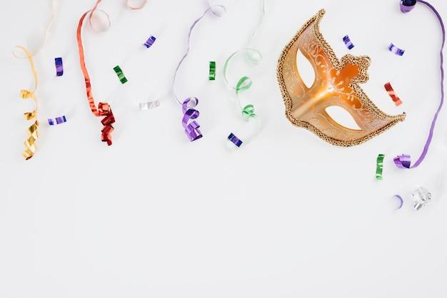 Máscara de carnaval con cintas de colores en la mesa