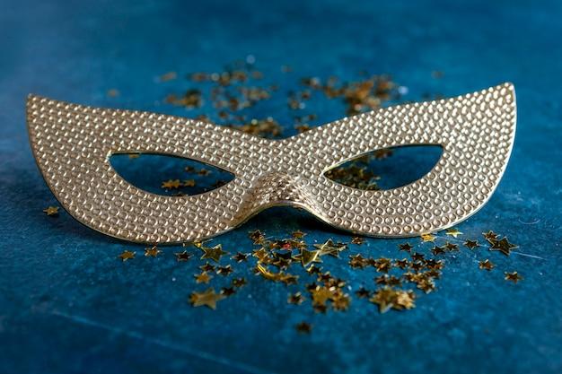 Máscara de carnaval y confeti dorado brillo