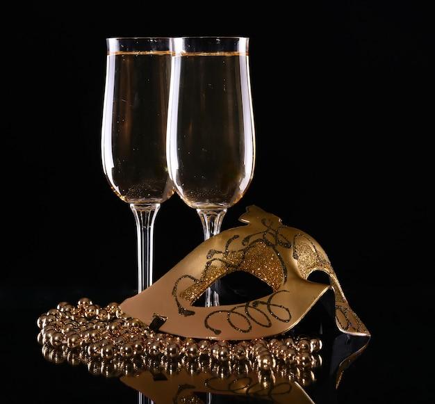 Máscara de carnaval y copas con champán sobre un fondo oscuro