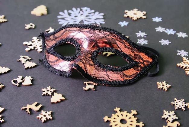 Máscara de carnaval y decoración de año nuevo sobre fondo oscuro.