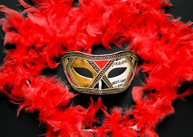 Máscara de carnaval dorado con boa de plumas rojas
