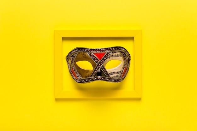 Máscara de carnaval dorado en marco amarillo