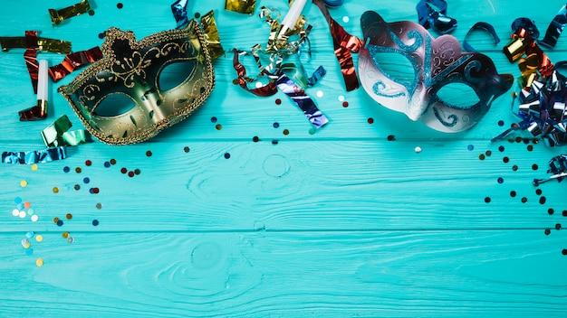 Máscara de carnaval de dos disfraces con decoraciones de fiesta sobre mesa de madera azul