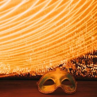 Máscara de carnaval frente a la brillante tela de lentejuelas con luces curvas