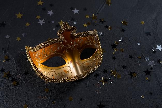 Máscara de carnaval con lentejuelas en mesa oscura
