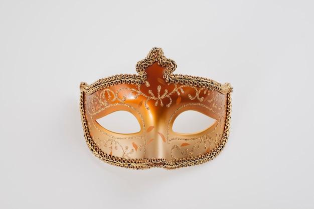 Máscara de carnaval naranja en mesa blanca