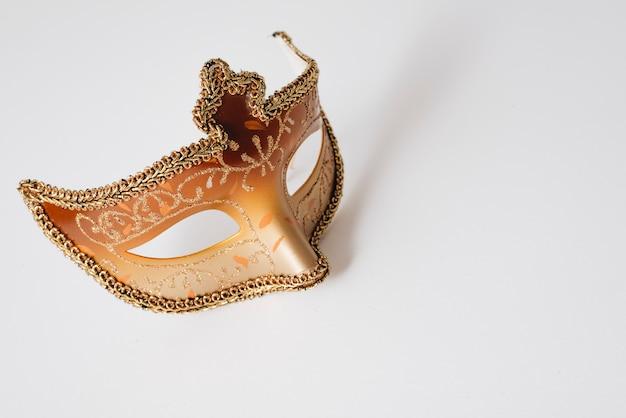 Máscara de carnaval naranja en mesa de luz