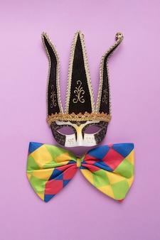 Máscara de carnaval negra con pajarita colorida