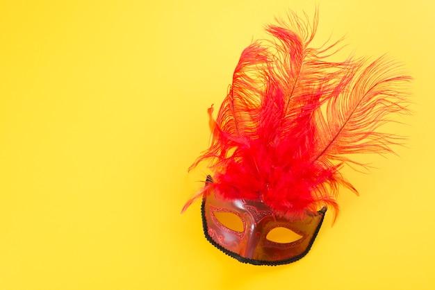 Máscara de carnaval con pluma en mesa
