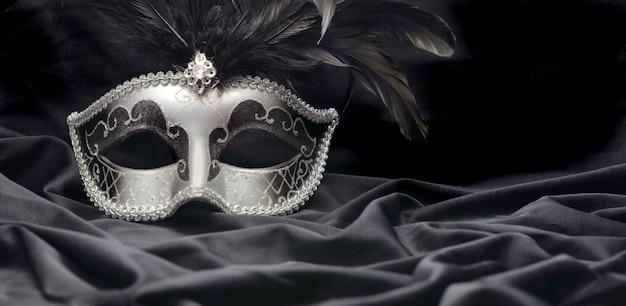 Máscara de carnaval con pluma sobre tela de raso