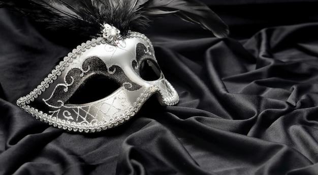 Máscara de carnaval con pluma sobre tela de satén oscuro