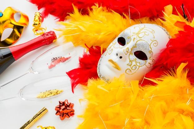 Máscara de carnaval con plumas y champaña.