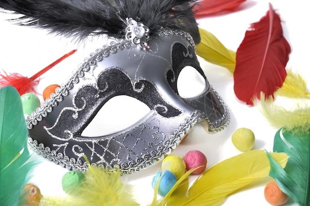 Máscara de carnaval entre plumas de colores