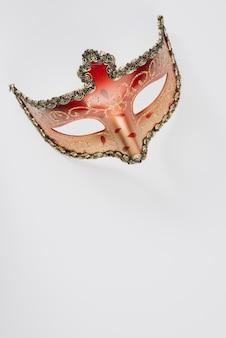 Máscara de carnaval rojo en mesa blanca