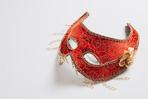 Máscara de carnaval rojo en mesa de luz
