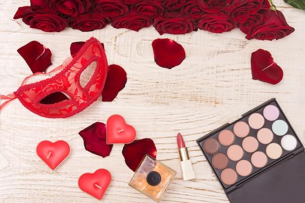 Máscara de carnaval rojo, ramo de rosas rojas, lápiz labial, botella de perfume y sombra de ojos sobre fondo de madera clara.