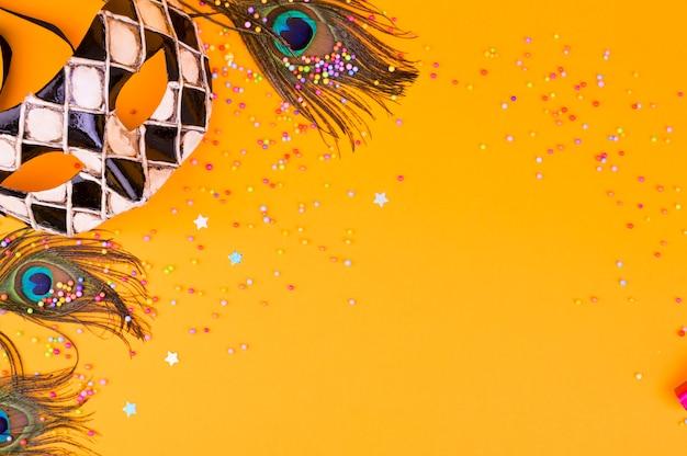 Máscara de carnaval sobre un fondo amarillo. decoración para unas vacaciones tradicionales italianas. copia espacio lay flat