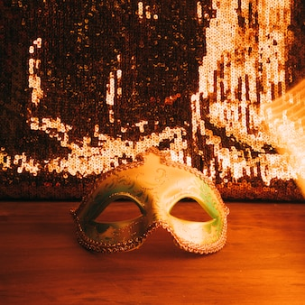 Máscara de carnaval verde en el escritorio de madera con lentejuelas doradas brillantes