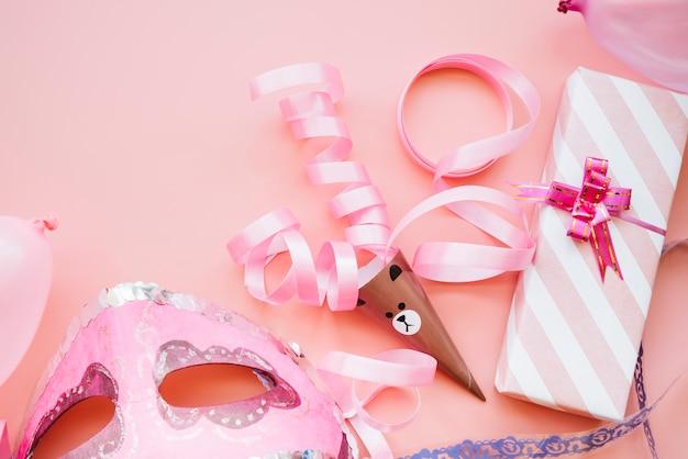 Máscara cerca de cinta y caja de regalo.