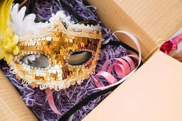 Máscara cerca de cinta colocada en caja artesanal