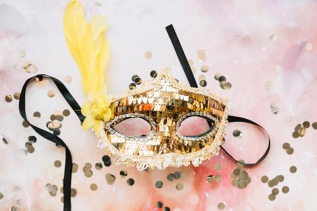 Máscara dorada brillante con plumas.