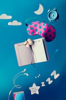 Máscara para dormir, agenda, reloj despertador, flores de algodón y elementos de papel, calidad de levitación del concepto de sueño con teléfono móvil y auriculares