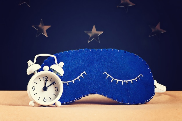Máscara de dormir hecha a mano de fieltro, estrellas sobre fondo negro.