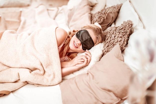 Máscara para dormir puesta. mujer tranquila y tranquila que ve sueños mientras duerme en un acogedor mal y está cubierta con una manta