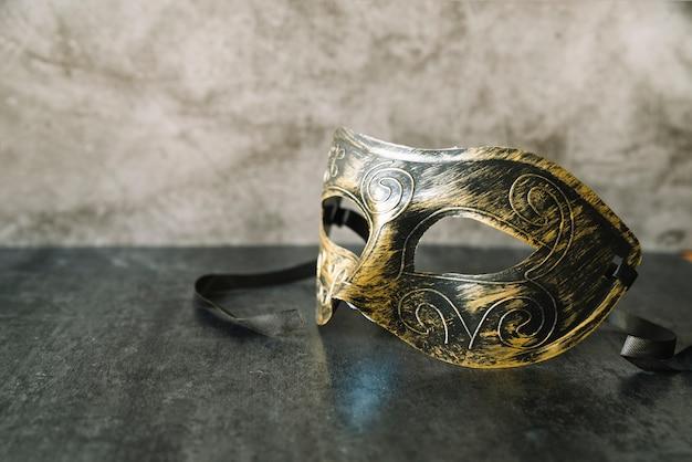 Máscara elegante con pintura dorada y negra.
