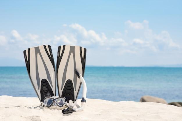 Máscara de esnórquel blanco y aletas en el destino de vacaciones de viaje tropical en la playa en tailandia, concepto de vacaciones de verano