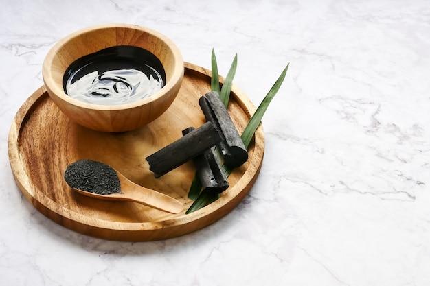 Máscara facial y exfoliante por polvo de carbón activado en la mesa de mármol