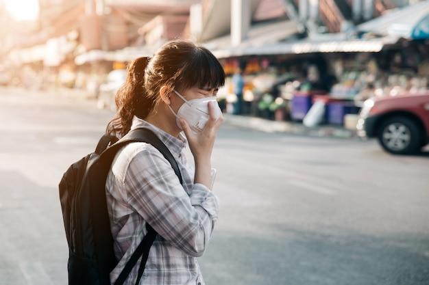 Máscara facial que lleva de la mujer asiática que tose debido a la contaminación atmosférica en la ciudad