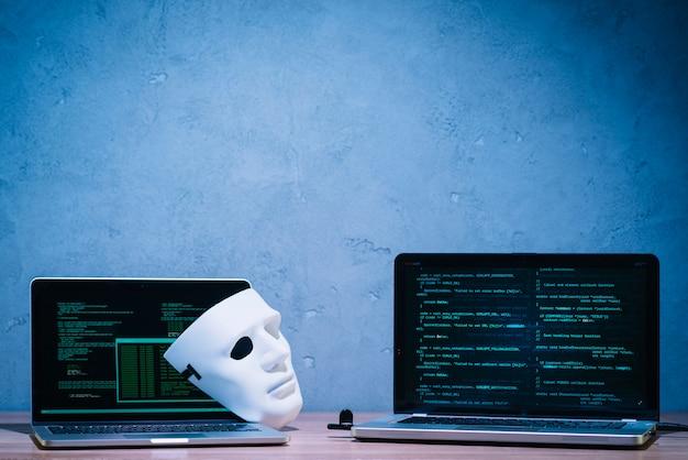 Máscara de hacker y portátil