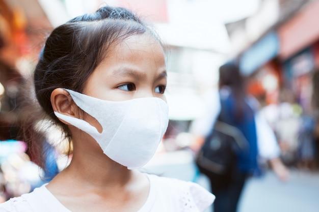 Máscara linda de la protección de la muchacha asiática linda del niño que lleva a contra la contaminación de la niebla con humo del aire